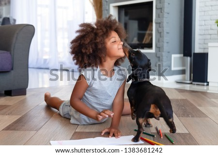 Photo of Funny little African American girl lying on floor coloring picture having fun with dog, family pet kissing playing with small child painting at home, kid laugh entertaining with domestic animal