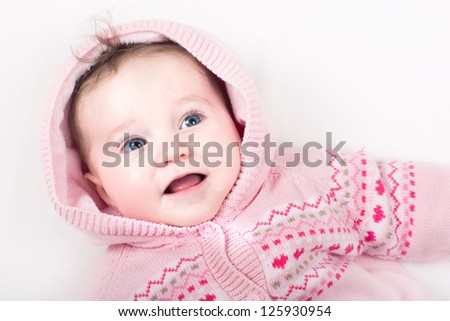 Funny little baby girl in a pink jacket with hearts pattern