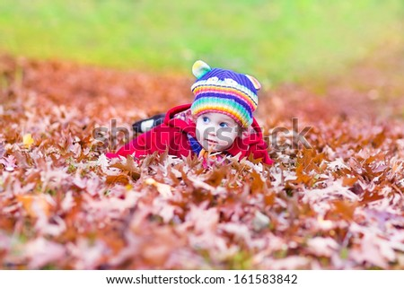 Funny little baby girl playing with colorful red autumn leaves