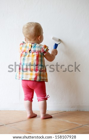 Funny little baby girl plays indoors during repair work in the house paining wall holding roll in her hands