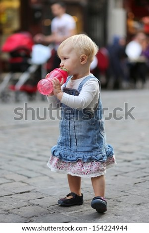 Funny little baby girl walks on a busy street drinking water from plastic feeding bottle, in background people are sitting eating in cafe