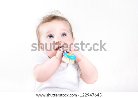 Funny little baby playing with a hair brush