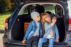 Funny little boy and his pretty fashionable sister with blond hair taking photos on modern smart phone sitting in the opened car's trunk. Family vacation trip by car.