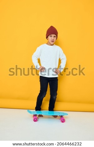 Funny little boy in a red hat skateboard in his hands Childhood lifestyle concept