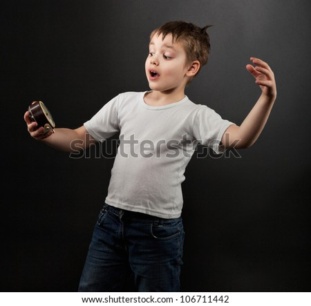 Funny little boy looking at alarm clock in shock