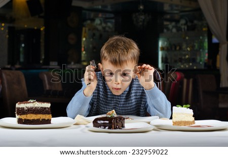 Funny little boy mesmerised by an assortment of cakes displayed on the dining table in front of him as he tries to make a choice where to begin eating