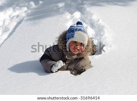 Funny little boy playing in snow, outdoors in winter.