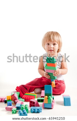 Funny little boy playing with blocks, studio shot