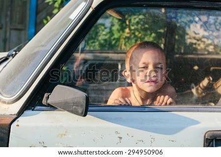Funny little boy pressed against the glass in old car and thinking