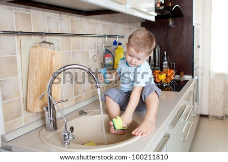 funny little boy sitting on kitchen table