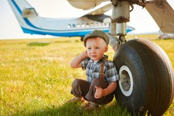 Funny little boy traveler sits near the landing gear of the plane and waits for the flight