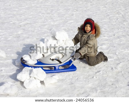 Funny little boy with sledge, outdoors in winter. - stock photo