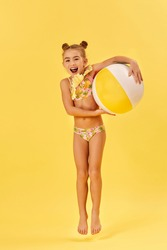 funny little child girl in swimsuit with beach ball jumping on yellow background