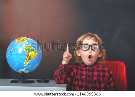 Funny little child in glasses pointing up. Showing place on the globe with blackboard on background. Pupil from primary school. first day of fall. Education, Success, bright idea, creative idea.
