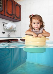 Funny little child swim in pan in the flooded kitchen, mess creative concept