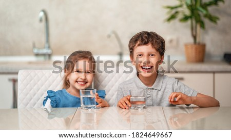 Funny little children drink water in the kitchen at home. The boy and girl are smiling happily, holding a glass of clean water and want to drink water. Water balance. Prevention of dehydration.