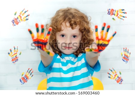 Funny little curly girl with hands in the paint. On a light background with colored prints of paint.