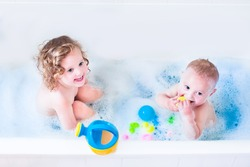 Funny little girl and her cute baby brother having fun taking bath together playing in water with foam with colorful toys after shower