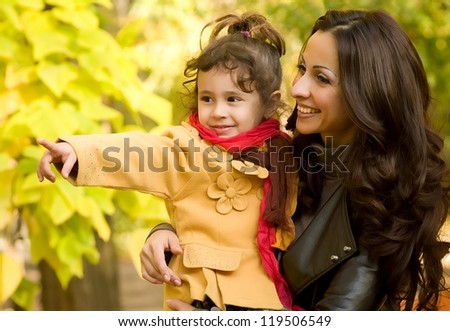 Funny little girl and mother in autumn forest