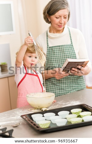 Funny little girl baking cupcake with grandmother hold whisk