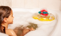 Funny little girl bathes in a bath with foam and plays life saving ball and swimming goggles. Children leisure at home concept. Copyspace