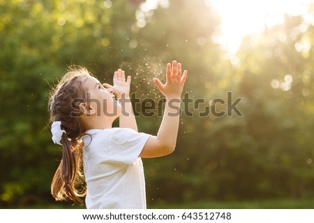 Funny little girl catching soap bubbles in the summer on nature little girl, has happy fun with cheerful smiling face. Carefree child Running and jumping on green summer meadow, catching soap bubbles