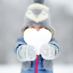 Funny little girl holding snow heart in beautiful winter park during snowfall