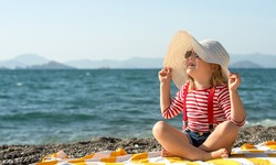 Funny little girl in a big striped hat on the beach. Kid in a hat and sunglasses on the beach. Happy little child on summer vacation.