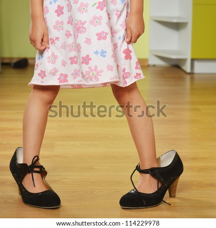Funny little girl in her mother's big shoes