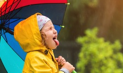 Funny little girl in yellow waterproof coat. Kid face with open mouth catching drops. Child with colorful umbrella playing in the garden under autumn rain.