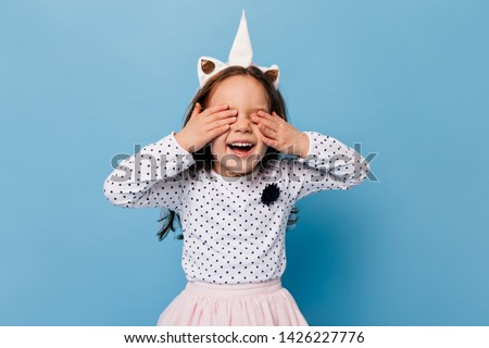 Funny little girl laughs with her eyes closed. Child in image of unicorn having fun on blue background