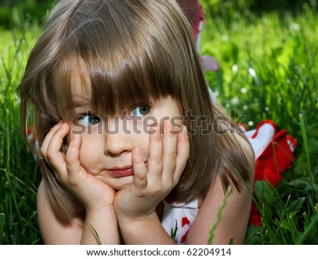 funny little girl lying in green grass close up