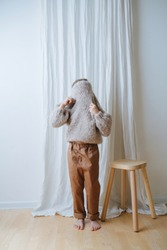 Funny little girl playing with a beige knitted sweater. She pulled collar over head, looking through tiny holes in a fabric. At home, in front of a curtain. Full length.