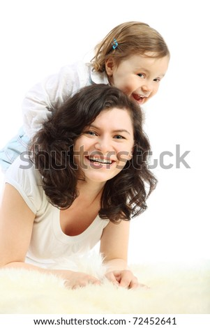 Funny little girl sits on mother which lying on white fluffy rug - stock photo