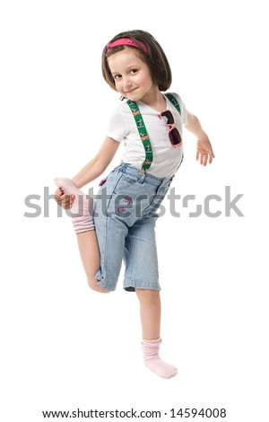 Funny little girl standing on one leg. Isolated over white background