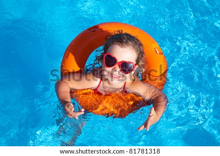 Funny little girl swims in a pool in an orange life preserver