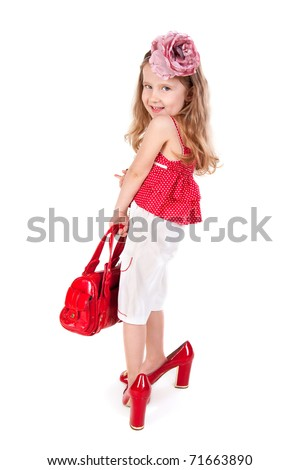 Funny little girl trying on her mother's accessories and shoes