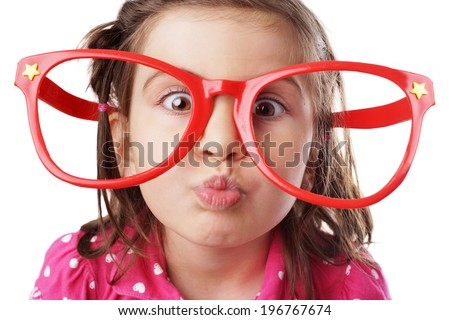 Funny little girl with big red glasses making face
