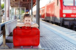 Funny little girl with big red suitcase on a railway station. Kid waiting for train and happy about traveling.