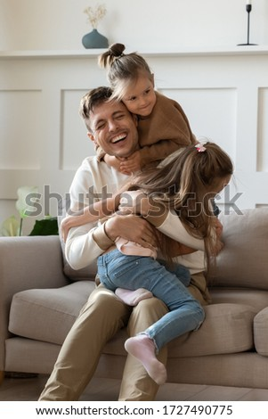 Funny little girls hugging cuddling smiling laughing father sitting on comfortable couch in living room, excited father having fun with two adorable little daughters, enjoying free time together