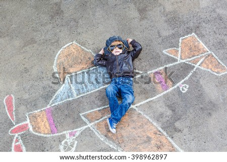 Funny little kid boy flying by a plane picture painting with colorful chalk. Creative leisure for children outdoors in summer. Child playing the little prince figure.