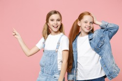 Funny little kids girls 12-13 years old in white t-shirt denim clothes isolated on pink background. Childhood lifestyle concept. Mock up copy space. Pointing index finger aside up, put hand on head