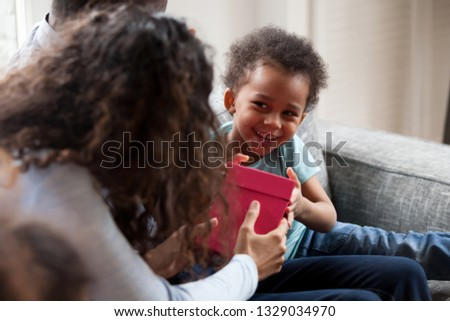 Funny little mixed race toddler boy give birthday present to mom sitting together with parents on couch, cute small African American kid laugh making gift box surprise to young mother