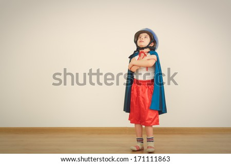 Funny little power super hero child (boy) in a blue raincoat.  Superhero concept