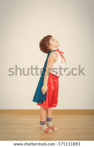 Funny little power super hero child (boy) in a blue raincoat.  Superhero concept