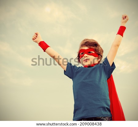 Funny little power super hero child (boy) in a red raincoat. Superhero concept