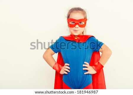 Funny little power super hero child (girl) in a blue raincoat. Superhero concept