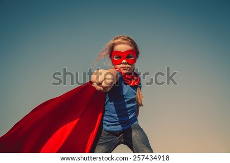 Funny little power super hero child (girl) in a red raincoat. Superhero concept. Instagram colors toning