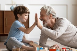 Funny little school boy giving high five to joyful middle aged hoary grandfather, playing together at home. Happy small grandson having fun with carefree cheerful older mature grandpa in living room.