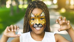 Funny little tiger. Adorable african-american girl with creative face painting roaring, playing wild cat outdoors